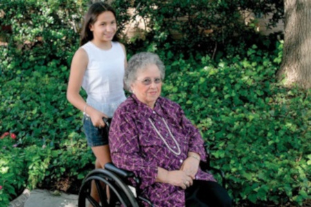 Older adult woman in wheelchair with child, Grandmother and granddaughter