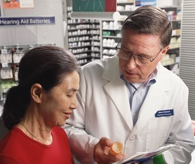 Image of patient and doctor looking at prescription bottles