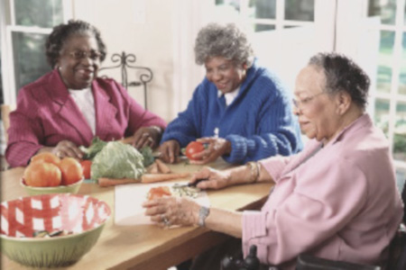 Image of three older African-American women, two sitting on chairs, and one in a wheelchair, gathered around a kitchen table with vegetables on the table.