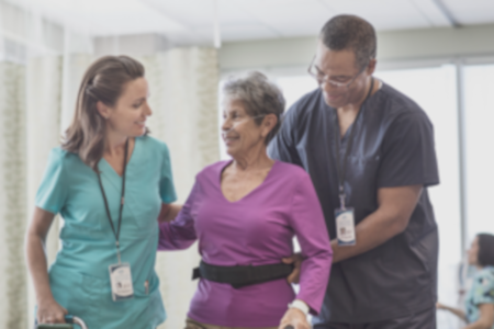 Two nurses helping patient walk