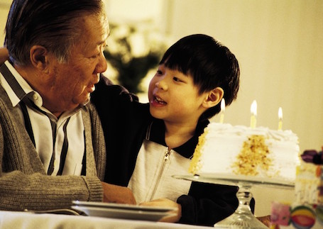 Old man and young child next to birthday cake