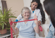 Doctor helping older patient with exercise using an elastic band