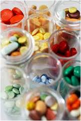 Image of several clear containers with various colored pills in each container.
