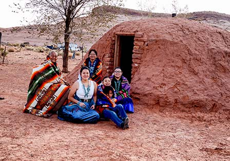 native american family sitting outside of an earthen dwelling